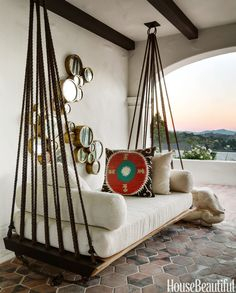 Responding to her clients' request for a swing where they could enjoy the view of Mount Tamalpais and the hills of San Francisco, Martin used rope, metal rings, and wood to improvise this hammock/divan on the loggia. Mirrors, Lucca Antiques.