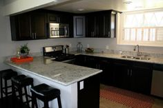 This hip and contemporary, black and white kitchen was transformed by HGTV's Flip or Flop team. Sleek black countertops and stone countertops create a sophisticated feel. A graphic, red and white rug adds a fun pop of color.
