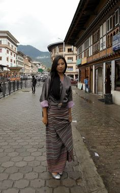 A young woman wearing a traditional Bhutanese robe. Previously all Bhutanese citizens were required to observe the national dress code, known as Driglam Namzha while in public during daylight hours. | 20 Beautiful Photos of People in Bhutan