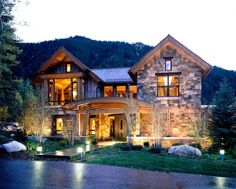 Front View Of The House With Stone Facade And Curved Wooden Porch Design Also Front Garden And Concrete Path Decorated By Fantastic Lighting And Mountain Background Scenery Mixed Design of the House Made of Natural Materials Home design