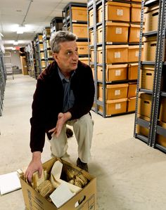State Archives and History Director Joe Geiger opens a box of circuit court records in their attic storage area at the Culture Center. As court records around the state are digitized, the state Division of Culture and History has collected historic circuit court records in an effort to preserve documents that counties may not be able to house