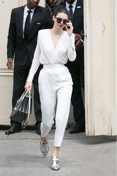 Kendall Jenner wears a white jumpsuit, metallic oxfords, sunglasses and a structured black bag.