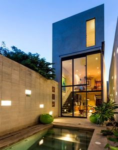 A narrow concrete house with a pool, wall of glass with metal frame, lofted living space and concrete side walls with built-in lighting. Click through for more images of this Mexico City home.