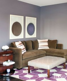 A graphic patterned rug grounds this cozy seating area, which boasts a tufted ottoman and a brown sectional sofa.