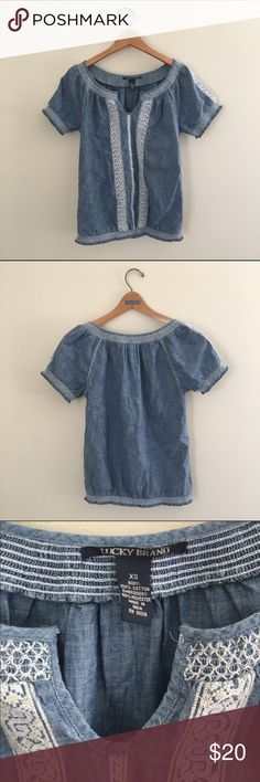 Lucky Brand Chambray embroidered top This top goes with everything! It is in great condition. Chambray style fabric with white embroidered pattern going down the front. Has an elastic band going around the bottom waist. Fits loosely above the elastic band. Lucky Brand Tops