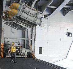 Boatswain's Mate 3rd Class Jonathon Perezandino signals to the inhaul/outhaul operator while in the hangar bay the aircraft carrier USS Theodore Roosevelt (CVN 71) during an ammunition offload with Military Sealift Command dry cargo and ammunition ship USNS Amelia Earhart (T-AKE 6).