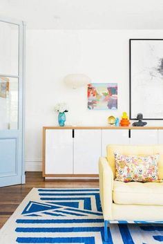 Bright living space with a yellow sofa, a colorful blue rug, and a dresser