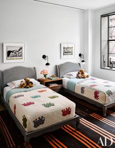 Images by Watts's brother, photographer Ben Watts, are displayed above RH Baby & Child beds in the boys' room; the pillowcases are by Ralph Lauren Home, the sconces are by Atelier de Troupe, the nightstand is by Room & Board, and the antique kilim is from Double Knot.