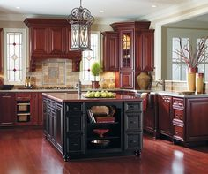 cherry wood kitchen cabinets with silver appliances and black