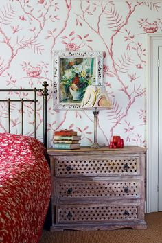"""The bedroom of this house designed by [link url=""""http://www.maxrollitt.com/""""]Max Rollitt[/link] relies on a colour scheme of contrasting colours and introduces an extra layer of cosiness via the textured picture frame and bedside chest of drawers. The antique quilt was matched to 'Jasper Peony' wallpaper, an Adam Calkin design from [link url=""""http://www.lewisandwood.co.uk/""""]Lewis & Wood[/link], while the lampshade is made from book paper and hand-painted by artist Madeleine Bradbury, whose…"""