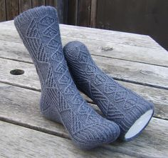 Chiana is a cuff-down sock with a fleegle heel, inspired by my favourite character from the sci-fi show Farscape. Like its namesake, Chiana is complex and challenging; full of twists, turns and angles. There are traveling stitches on every round and all charted knit stitches are twisted (knit through the back loop). Chiana is a monochromatic gal and so these socks are grey.