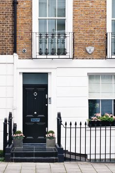 Black front door and box hedging on exterior of white painted ...