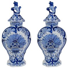 "A pair of Dutch Delft covered vases decorated in Blue and White with a dramatic design of a vase holding a symetrical arrangement of peacock feathers or ferns, and topped with leopard finials.  The bottoms of the vases have the mark of ""The Claw"". Circa 1780"