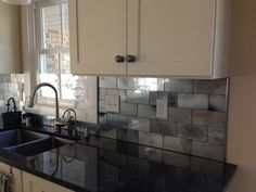 Faux mercury glass tile backsplash. Ann Sacks tiles would have been thousands of dollars and this DIY looks just as good! Lots of trials and tribulations but all good. Clear glass tiles cut, paint one side; goes on the wall with glass side out. Used lots of layers, mirror, silver, and specs of black spray paint for extra aging. Attaching with silicone calk worked the best. Love the results!