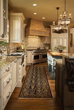 Twin chandeliers hang over one of two islands in this richly detailed kitchen. Natural hardwood floors, painted cabinet surrounds, marble countertops and patterned tile backsplash complete the look. (Note the painted island!!)