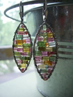 These earrings are made with watermelon tourmaline beads woven inside sterling silver marquise shapes .They resemble stained glass windows.The light shines through them beautifully.They are incredibly lightweight and each pair is Ooak.  The earrings are 1.5 inches long and 1/2 inch across .  Theyve been slightly oxidized and hang from sterling silver lever backs for safety.