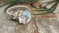 Mercury Mist 10 mm stone set in handmade sterling silver ring. This is a solitaire wire wrapped setting that cannot be adjusted to a different size.  Mystic Topaz have to be taken care of and cleaned carefully so they do not loose there luster. Just use a mild soap and
