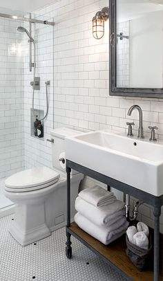 Industrial bathroom with white subway wall tiles and black & white penny floor tiles.