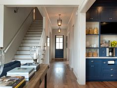 This long white foyer and hallway is crisp and elegant with minimal furnishings and lantern pendant lights. The navy blue door picks up the blue of the kitchen cabinets unifying the home's design scheme.