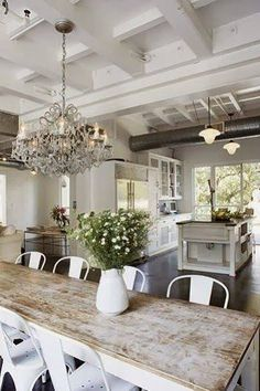 White-washed rustic kitchen with chandelier.
