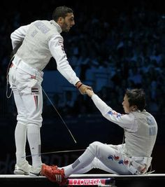 Alaaeldin Abouelkassem of Egypt, left, helps opponent Choi Byungchul of South Korea during their semi-finals of the men's individual foil fencing match at the 2012 Summer Olympics, Tuesday, July 31, 2012, in London. (AP Photo/Dmitry Lovetsky)