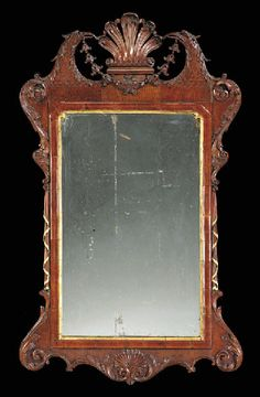 AN IRISH GEORGE II MAHOGANY AND PARCEL-GILT MIRROR  Circa 1740  The later rectangular plate within a panelled surround and outset corners, surmounted by a pierced shell, flanked by eagles' heads with bellflowers hanging from their mouths, the sides with scrolling acanthus, the shaped base centered by a shell, regilt  46in. (117cm.) high, 27in. (68.5cm.) wide Mirror Photo Frames, Wall Mirror, Color Of The Day, Unique Furniture, Interior Accessories, Interior Decorating, Antique Mirrors, Carving, Bronze