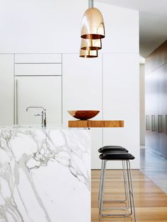 White marble island in kitchen with black stools and gold hanging lamps
