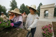 Workers unload flower pots near a replica of the Arc de Triomphe in Beijing, July 25, 2008. (© Claro Cortes IV/Reuters)