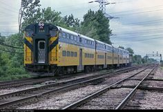 """A CNW """"Scoot"""" heads northwest on CNW""""s Harvard line at Des Plaines, IL. The train is about to cross the Soo Line diamond and will cross the CNW freight line in a quarter mile. These diamonds were protected at this time by Deval tower."""