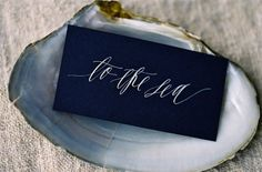 Escort card idea - hand calligraphed escort cards placed in shells for a nautical wedding