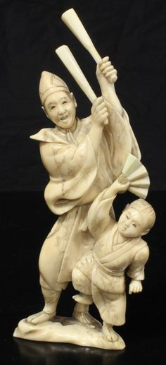 Japanese hand carved ivory figure depicting a man and child doing a ceremonial dance. Then man is holding drum mallets and the boy a folding fan. Signed to bottom. 18th/19th century.