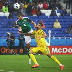 Gareth McAuley (L) of Northern Ireland scores the opening goal during their UEFA EURO 2016 Group C match against Ukraine