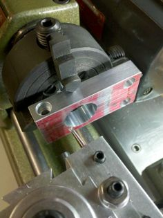 "Creating an intermediate pulley bearing holder for the Unimat milling head. In this set-up, two of the chuck jaws in the 4-jaw chuck are reversed. In another set-up I used 1/32"" thick slotting saw to cut a slot from the left edge to the bored hole. A cap head screw (hole is visible on top edge) is used to clamp the pulley bearing after slotting the edge. Should have used brass shims to protect the part from chuck jaw marks."