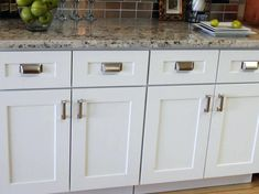 Antique White Cabinets are a beautiful hand painted antique white with a rich golden brown accent around the features of the door. #Antique #White, #Kitchen #Cabinets