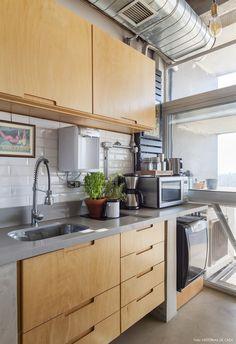 Cozinha tem estilo industrial e marcenaria com madeira clara e subway tiles.