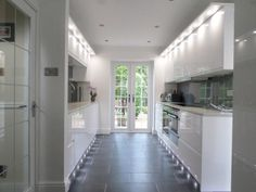 Light galley kitchen in Second Natures handleless Remo range designed and installed by Anglia Interiors - http://www.sncollection.co.uk/real-kitchens/real-kitchen-projects/remo-gloss-white-anglia-interiors.html