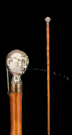 Perfect for the young-at-heart prankster, this charming walking stick  spits! The knob takes the form of a man's head, who, with the push of a  lever, spits water at any unlucky passerby. The delightful handle rests  atop a bamboo shaft ~ system canes and walking sticks ~ M.S. Rau Antiques