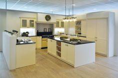 Landelijke, witte keuken in een U-vorm met een kookeiland als middelpunt. Door de vele keukenkasten in verschillende formaten en modellen heeft deze keuken eindeloze opbergmogelijkheden.