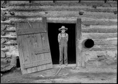 North Carolina Farm Boy in Doorway of tobacco barn. Person County, North Carolina. Photographed by Dorothea Lange in July of 1939 on nitrate 2 1/4 inch film for the WPA.