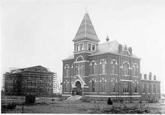 The main building, later named Samford Hall, is shown under construction in 1888-90 after Old Main burned.  Samford housed administrative and faculty offices, and classes were taught there from 1890 until about 1969.  While Samford was being built, classes were held next door in Langdon Hall, hidden from view here by the Chemistry Building (now Hargis Hall) at right.  Hargis was completed while the main building was still under construction.  Young George Petrie taught six hours--French…