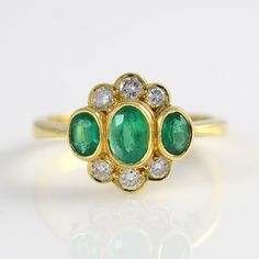 Estate 18 karat yellow gold ring with a center oval emerald at 0.45 carat and two side oval emeralds at 0.30 carat total weight and six diamonds