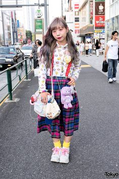 Aug 2014: Chun is wearing a long sleeve Tweety Bird shirt from New York Joe Exchange (the shop she works at) along with a plaid pleated midi skirt (also from New York Joe), yellow socks, and platform Volatile sneakers that she picked up resale. Accessories include a Care Bear, a Charlie Brown cap, a resale bag decorated with charms and ribbons, cute suspenders from KiloStore, various buttons, a vial necklace, a Furby ring from Ropeway, a ballet shoes ring from Yakusoku, and a colorful…