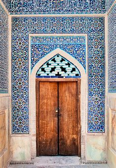 Simple wooden door in breathtakingly detailed frame. Isfahan, Iran. More on Iran, on theculturetrip.com
