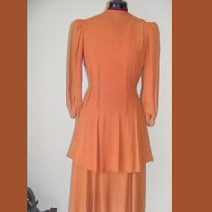 "Vintage 20s Pumpkin Rayon Crepe 2pc Flapper Dress This set from the late 20s It is rayon with button accents, Puff sleeves & attached tie belt. has an under dress with the top/Over dress. The under dress has rayon skirt portion & silk bodice with hidden metal side snaps. The outer dress has perfect working metal back zipper. It is pumpkin orange. It is in very good condition.  there is some faint fading on the dress but. No holes measurements are 36"" in the bust 26"" around the waist 44"" in…"