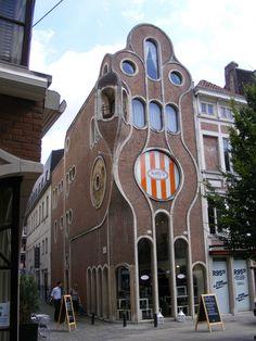 Фасад коричневого цвета в модерна стиле с необычными окнами