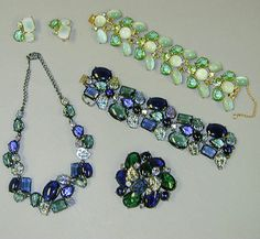 Group of Schiaparelli Jewelry 1950s Comprising a suite including a necklace, bracelet and pin, each with large smoky green and blue stones trimmed with iridescent carved leaves, marked; and a bracelet and earrings, each with milky green stones and green rhinestones, marked.
