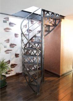 DH87 - SPIR'DÉCO® San Francisco. Escalier hélicoïdal d'intérieur d'accès mezzanine en acier au design industriel pour une décoration de caractère. Marches Nanoacoustic® tôle striée pour un escalier tout métal silencieux. Contremarches et limon découpés façon charpente à l'ancienne avec rivets forgés. Rampe soulignant les courbes naturelles de l'escalier en colimaçon. Finition : acier brut patiné. - Modèle déposé - © Photo : Nicolas GRANDMAISON - ESCALIERS DÉCORS®