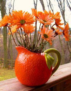 Orange pitcher with orange daisies