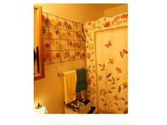 Metal flower wall hanging and quilt in front of plastic shower curtain for a different bathroom design look.