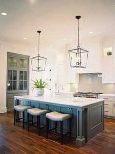 beatuiful kitchen inspiration with wood floors, blue island, hanging lanterns over an island, and white perimeter cabinetry. This is a dream kitchen! kitchens with blue islands, kitchens with built-in china cabinet